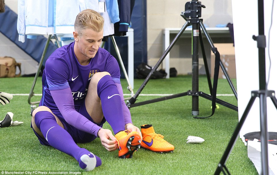 A behind-the-scenes photo from the Manchester City kit launch photo shoot sees first-choice keeper Hart putting on his boots