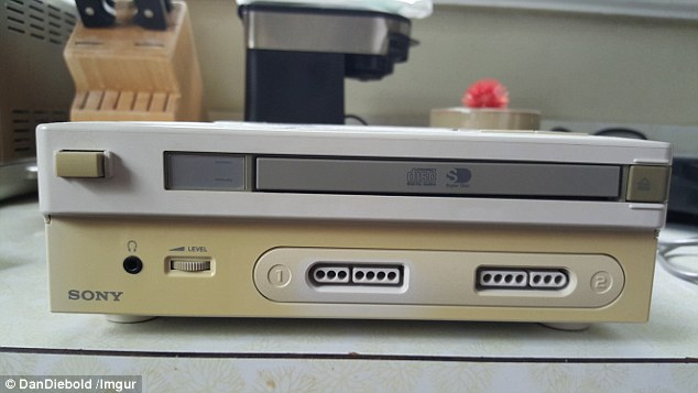 Old-school: The gray device has a CD port, pictured above, and Sony branding - but has slots which were used with SNES controls