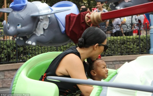 Excited: North appeared to be having the time of her life on the Dumbo ride with her mother Kim