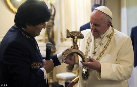 Unusual: Pope Francis receives the crucifix carved into a wooden hammer and sickle from President Evo Morales on Wednesday, after arriving in the Bolivian capital of La Paz