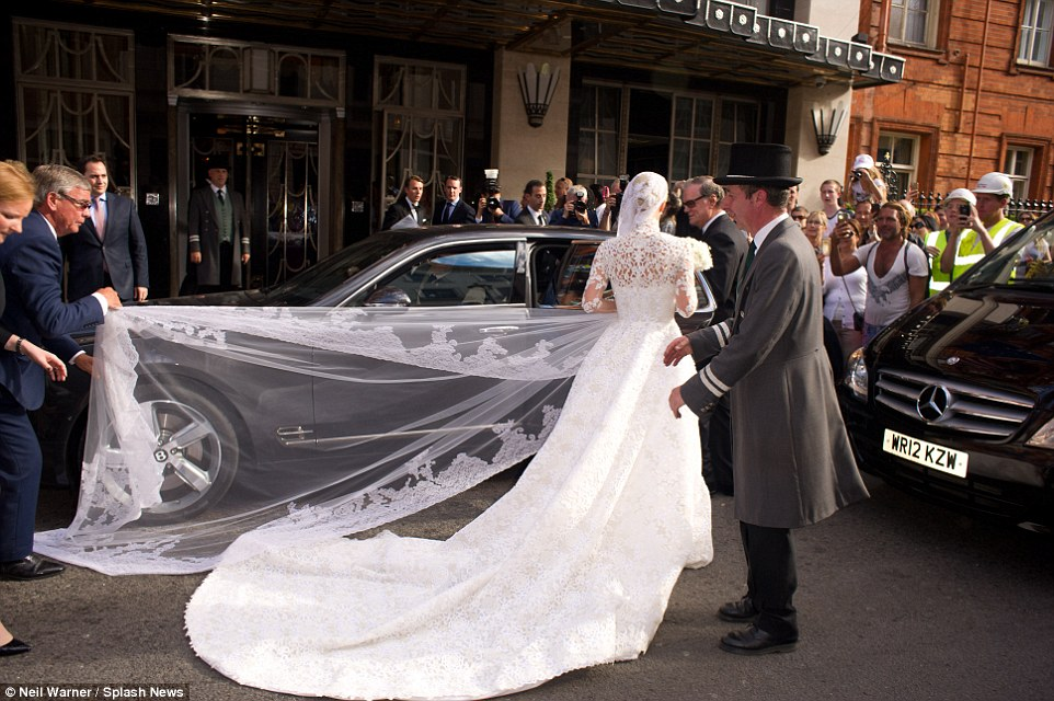 Stunning: Just as long as the train was the beautiful antique lace veil which proved just as troublesome to handle for the aides