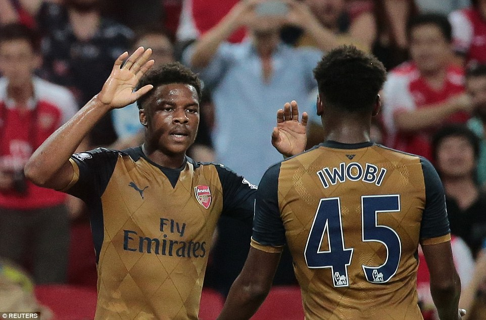 Arsenal forwardChuba Akpom celebrates with his team-mate Alex Iwobi after giving his side the lead against a Singapore Select XI