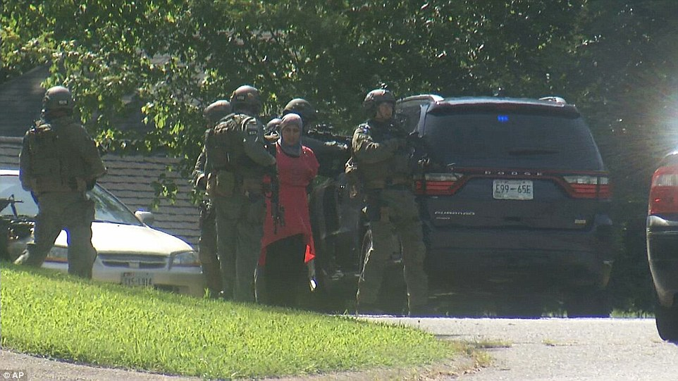 Raid: Law enforcement officers detain a woman as they surround a house in Hixson, Tennessee, where gunman Youssef Abdulazeez lived for almost 17 years
