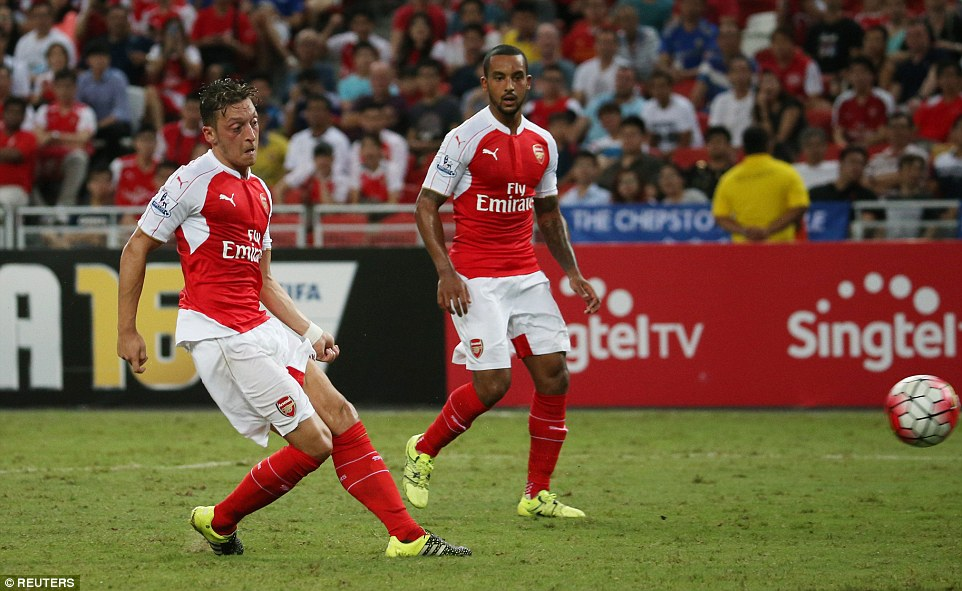 Ozil fires Arsenal into a three-goal lead as the German international grabs his first of the game as team-mate Walcott watches on in Asia