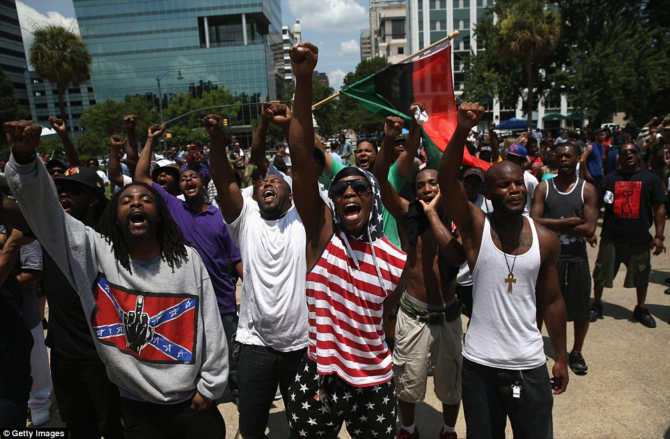 The group, which erupted into chants of 'black power', said the flag ceremony was an 'illusion of progress'