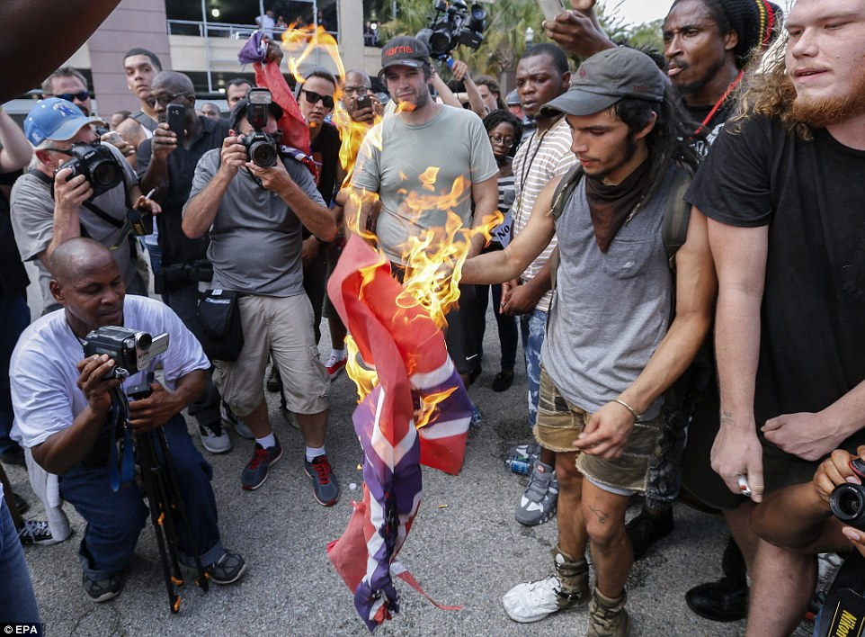 Symbol: A man is captured burning a Confederate flag in front of the statehouse steps surrounded by other anti-white supremacy protesters