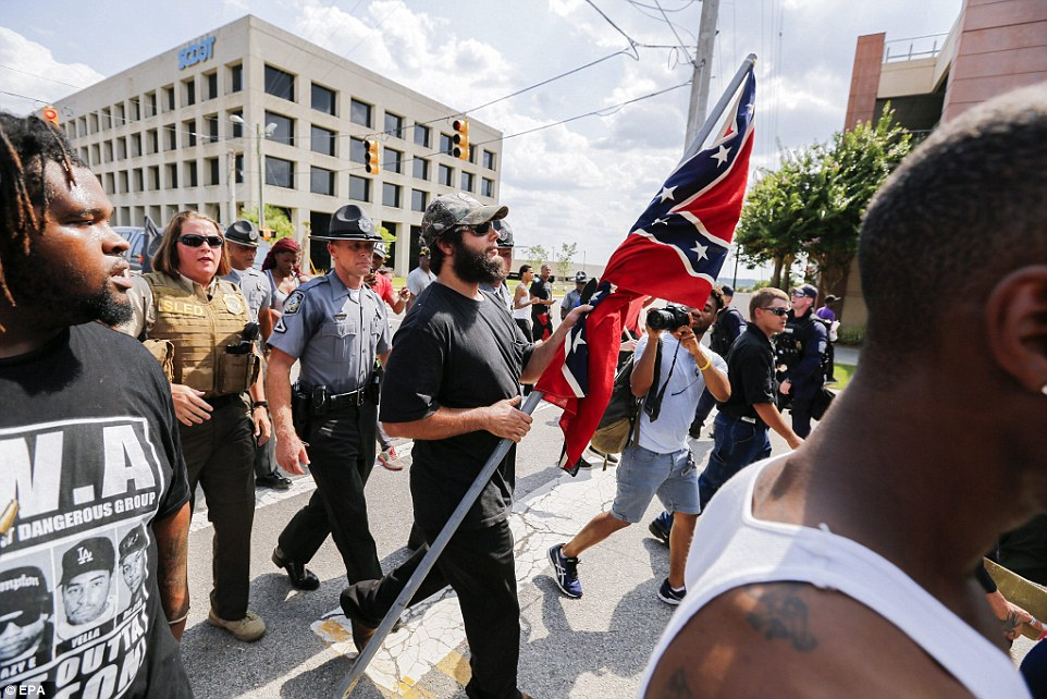 Police officers walk alongside white-supremacy protesters in a bid to keep relative calm during the demonstrations