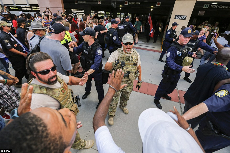 Law enforcement personnel, heavily armed and wearing body armor, try to keep opposing sides apart during the demonstrations