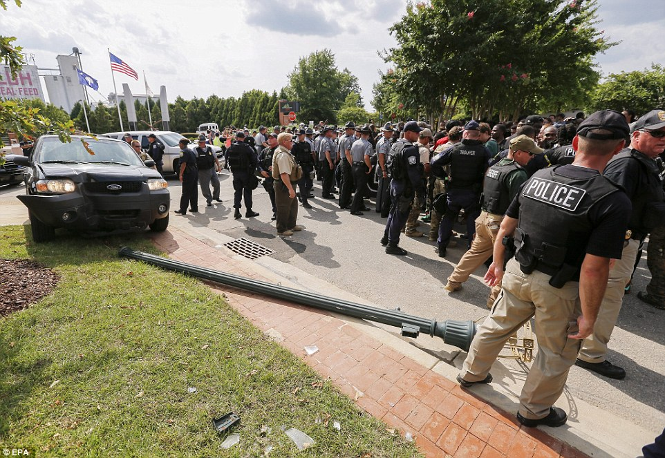 Police keep protesters back near a vehicle driven by a Klu Klux Klan member who knocked into a lamppost at the scene