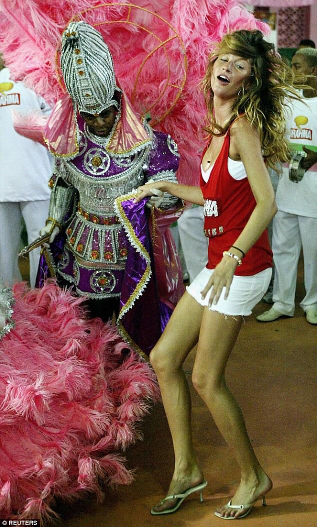 Supermodelo brasileira Gisele Bundchen dança com foliões no Rio de Janeiro, em 2004.