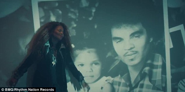 Family affair: She dances in front of a wall which features snaps of her with her father Joe