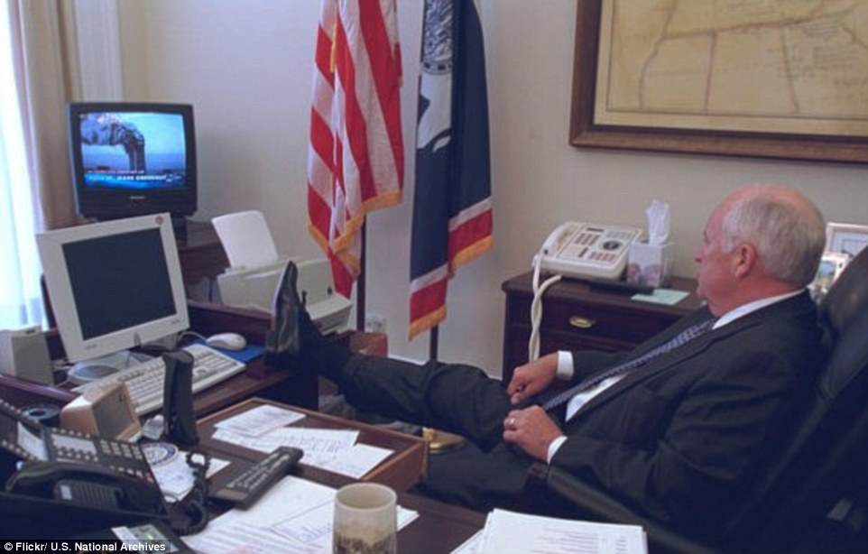 Taking it in: Then-Vice President Dick Cheney rests his feet on his desk as he watches a live TV news report of the 9/11 attacks on the morning of September 11, 2001. The first plane hit the WTC's North Tower at 8.46am. A second jet struck the South Tower at 9.03am