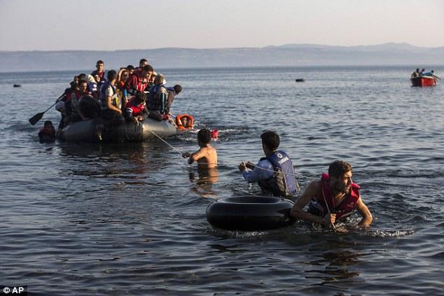 Migrantes tirar un bote abarrotado de refugiados sirios y afganos que llegan desde las costas turcas a la isla griega de Lesbos
