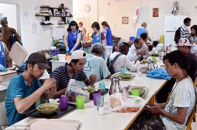 Los inmigrantes reciben una comida ofrecida por Cáritas Grecia en sus instalaciones en el centro de Atenas