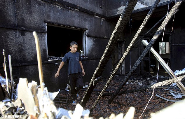 Torched: A boy inspects a house that was badly damaged from a suspected attack by Jewish extremists on two houses in Duma  near the West Bank city of Nablus which killed an eighteen-month Palestinian baby