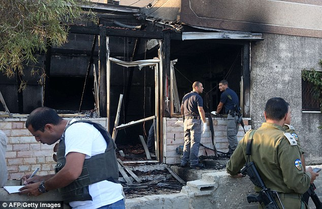 Israeli security forces inspect a Palestinian house that was set on fire by Jewish extremists in the West Bank