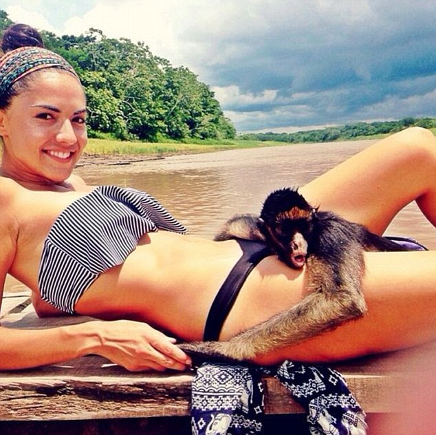 The model pictured relaxing by the Amazon River in Peru with Karina, a spider monkey and rescued ex-pet