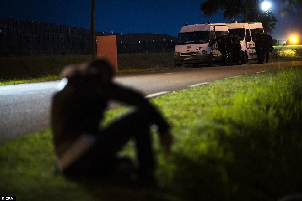 Un migrante espera una oportunidad para cruzar la valla que conduce a las pistas como policía francesa tratan de bloquear el acceso