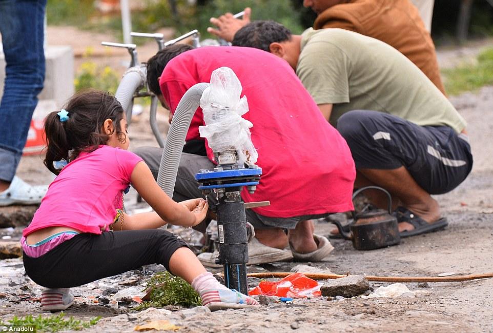 Una chica joven que se ve entre un grupo de migrantes de lavado en un campamento en el norte de Francia el día de hoy