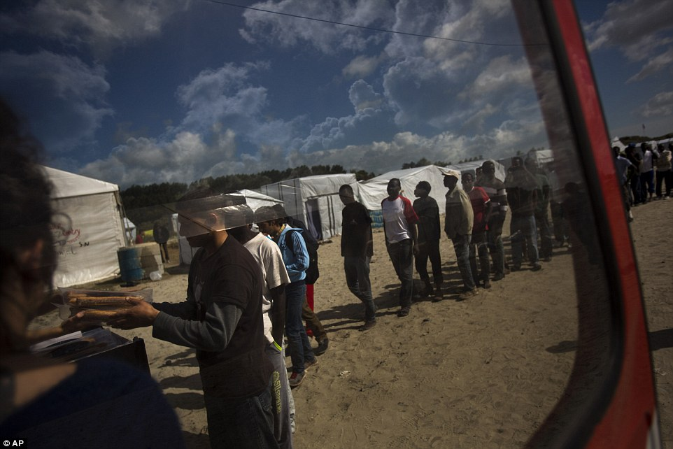 Las personas hacen cola para las raciones de alimentos distribuidas por el Banque Alimentaire de Calais en un campamento de inmigrantes el día de hoy