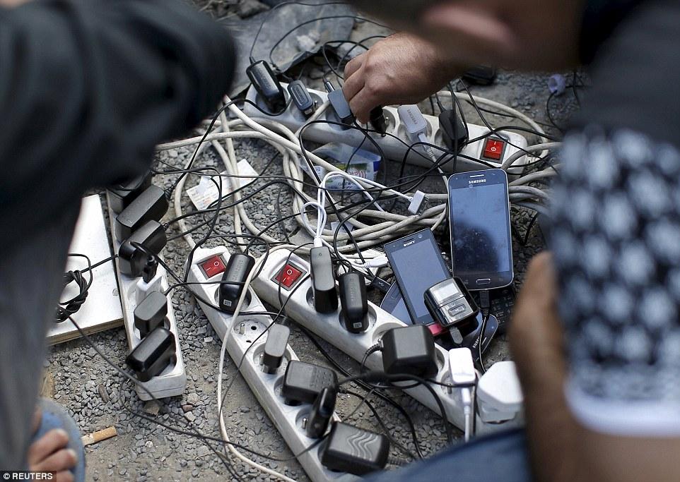 Electricidad: Los migrantes de carga sus teléfonos móviles en adaptadores multi-socket, alimentado por un generador, en el campamento de Nueva Selva en Calais