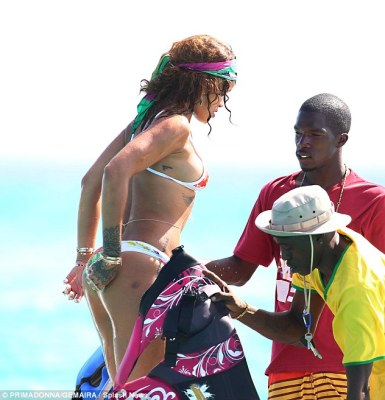 Beach babe: Rihanna flaunted her pert derriere in a teeny bikini as she enjoyed a day of watersports alongside rumoured love interest Lewis Hamilton on Friday