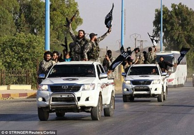 Militant Islamist fighters wave flags as they take part in a military parade along the streets of Syria's northern Raqqa province in 2014