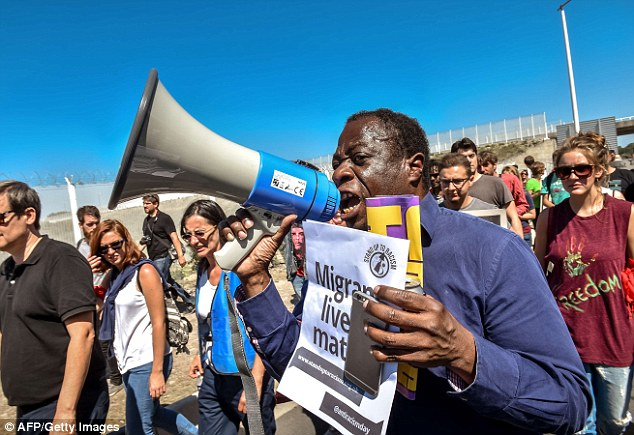 Making themselves heard: A man shouts slogans with a poster saying 'Migrants lives matter'