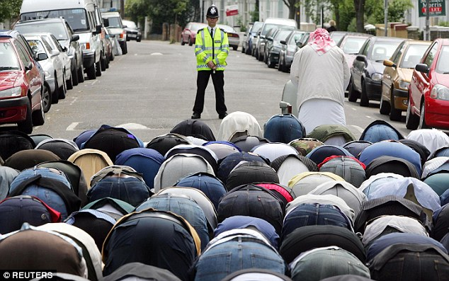 Defiant: British Muslims gather to worship in the street outside the Finsbury Park Mosque. The mosque was once frequented by the radical Muslim cleric Abu Hamza al-Masri, who is now serving a life sentence for terrorism charges