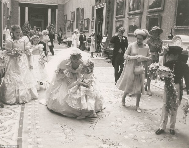 Ornate: Even in her wedding gown, Princess Diana is able to bend over to set down Clementine as they make their way through the palace