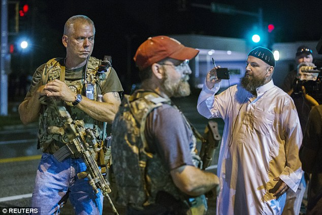 Armed patriots have been seen patrolling the streets of Ferguson with assault rifles in a move described by police chiefs as 'inflammatory'