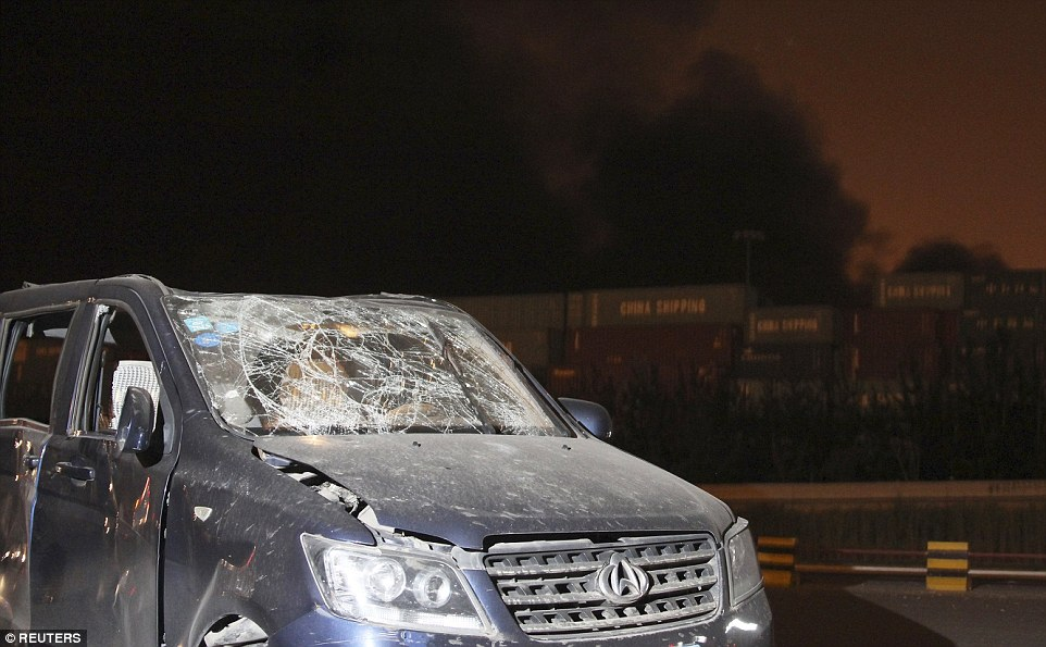 Crushed windscreen: A damaged vehicle is seen near the site of the blasts in Tianjin yesterday evening as the city learns of the incident