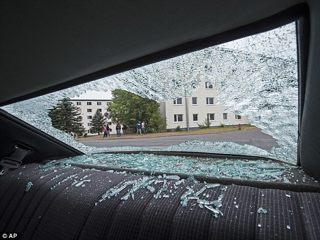 Demolished: Pictures from today showed how the angry refugees smashed car windows with steel rods