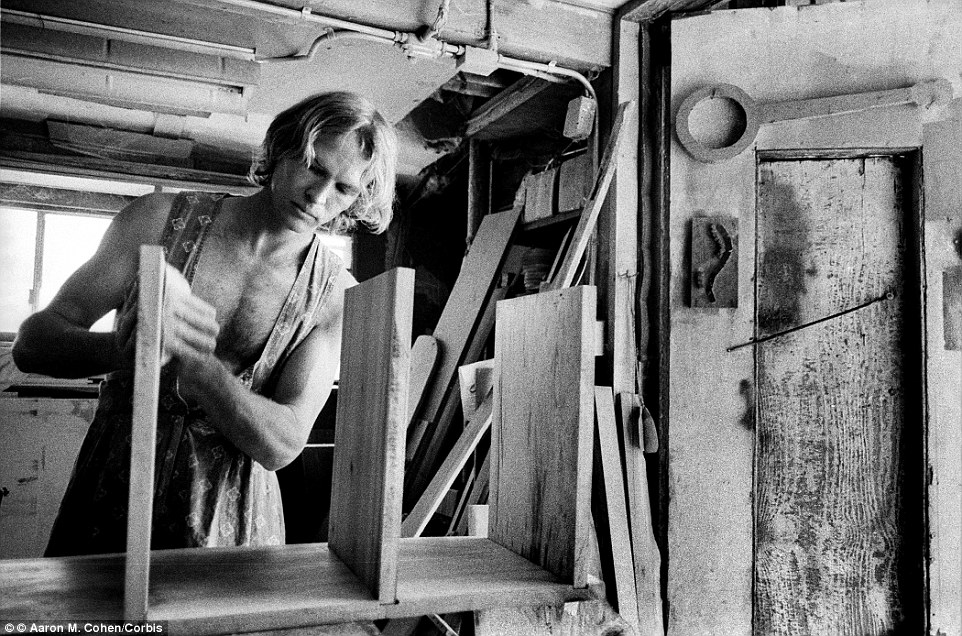 At work: A man named Hans wears a sundress while building shelves in the woodshop at the Twin Oaks commune in Virginia in 2005