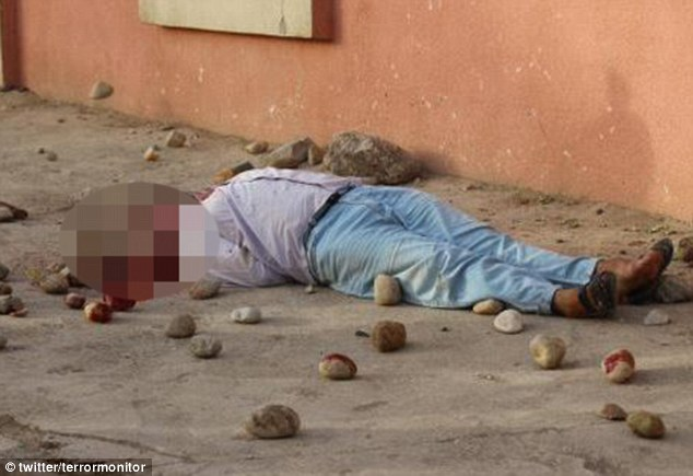 Pool of blood: The body of a man stoned to death, apparently for committing adultery, lies on the street in Nineveh, Iraq. The incident was the latest example of ISIS' barbarity