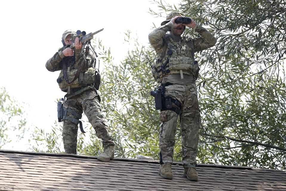 A sniper and a lookout stand on top of a roof searching for the three men following the killing of the officer. Reports suggest he was a 32-year veteran of the department