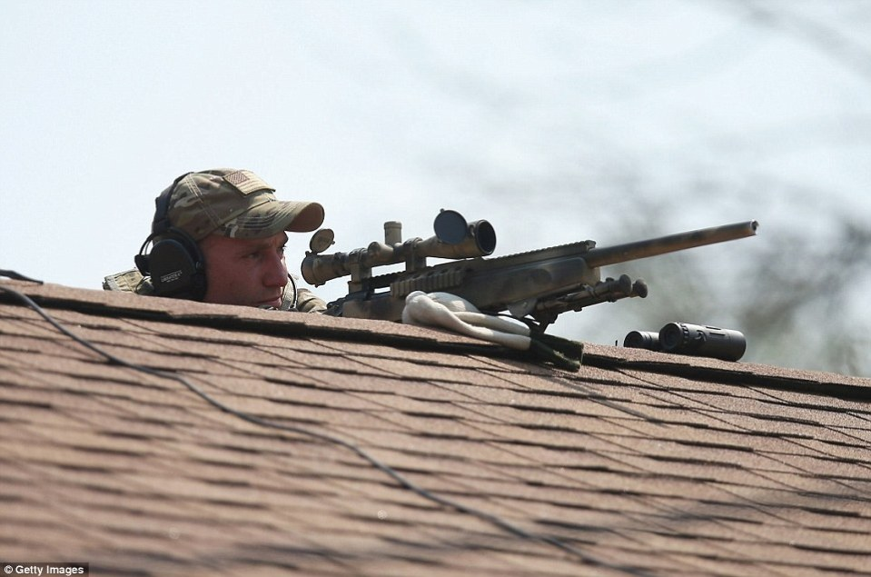 A sniper perches on top of a roof inside the search area. The FAA has also established a two-mile no-fly zone
