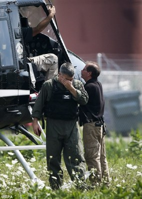 A law enforcement member wipes his eyes during a search for three armed suspects in the shooting of a Fox Lake police officer