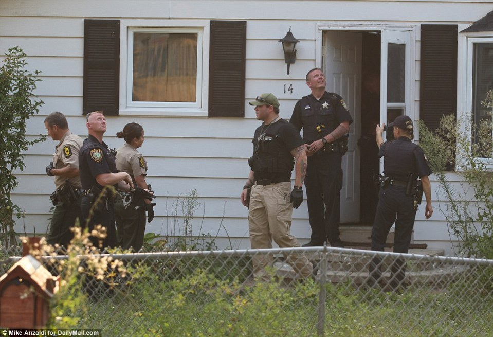 Police are seen leaving a house in the search area this afternoon. Schools were locked down for fear of the armed suspects