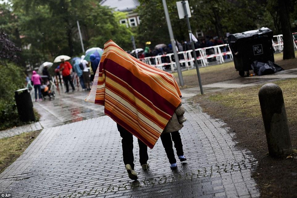 Fría y sola: Cubierto con una manta para protegerse de la lluvia a una mujer con una niña llega al centro de acogida de los refugiados y solicitantes de asilo en Berlín, Alemania