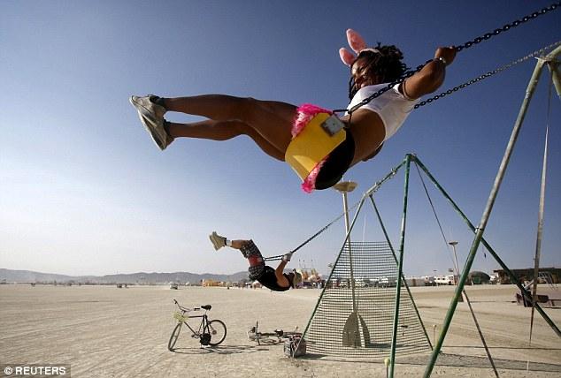 Playa name: Adorable, her Playa name, rides a swing during the Burning Man 2015