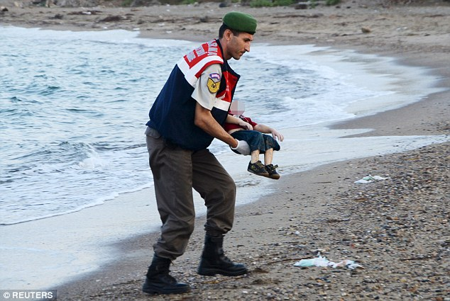 A policeman on a Turkish beach gently recovers the body of little Aylan, 3, who washed up on a beach