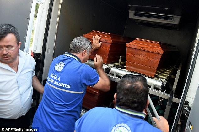 The coffins of some of the migrants who drowned being loaded into a funeral vehicle in southern Turkey