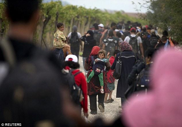 Los migrantes a pie por un camino de tierra después de cruzar la frontera entre Macedonia griega cerca de Gevgelija, Macedonia