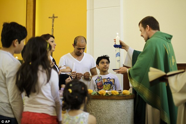 Pastor Gottfried Martens lights a candle during a service to baptise migrants from Iran at the Trinity Church in Berlin. Pictured third right is Mohammed Ali Zanoobi who is among hundreds ofmostly Iranian and Afghan asylum seekers who have converted to Christianity at the evangelical church in a leafy Berlin neighbourhood
