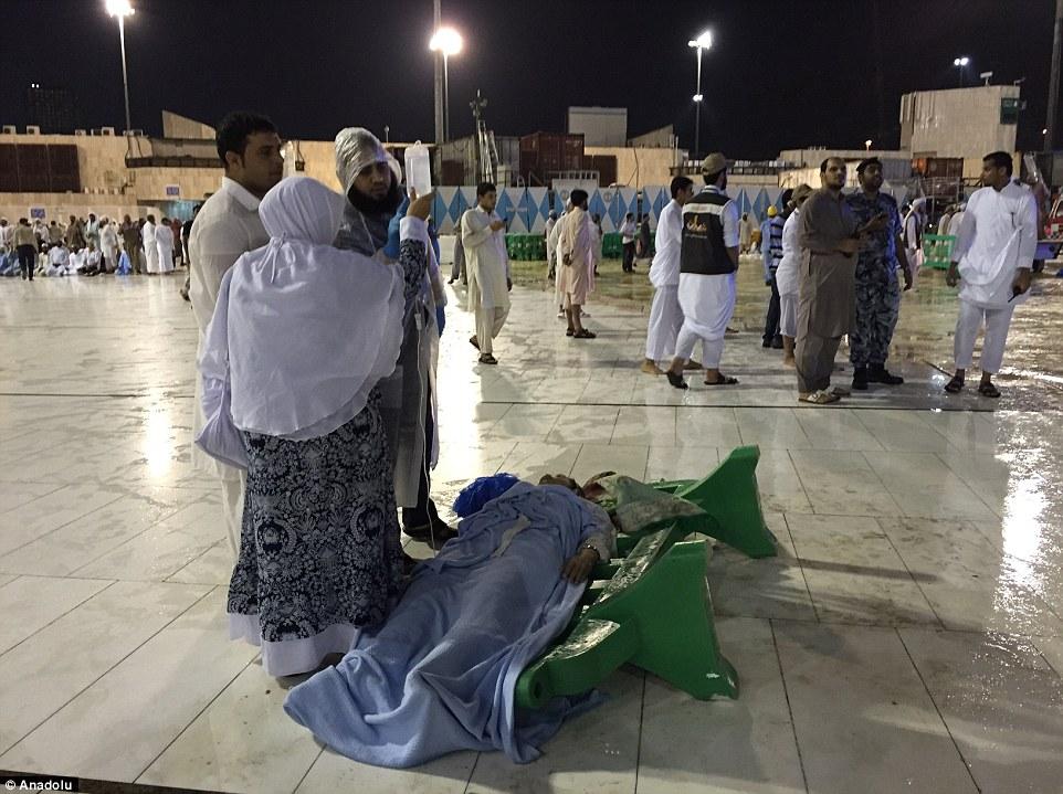Luchando por su vida: Un hombre se daña se encuentra en una camilla improvisada, cubierto de mantas, mientras que otros mantienen su goteo