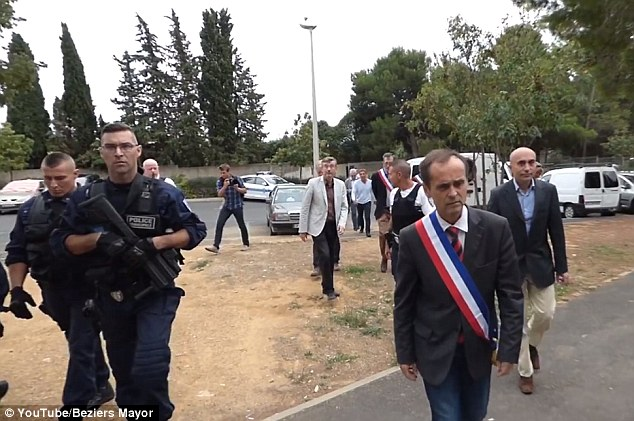 On a mission: Robert Menard is shown marching into a squat surrounded by police, including an armed guard