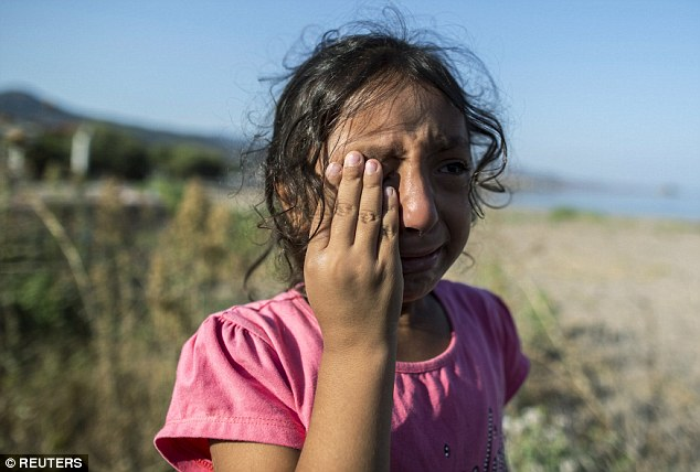 Tears: Yasmine, a six-year-old refugee from the ISIS-held Syrian city of Deir Al Zour bursts into tears of relief after arriving on the Greek island of Lesbos over the weekend