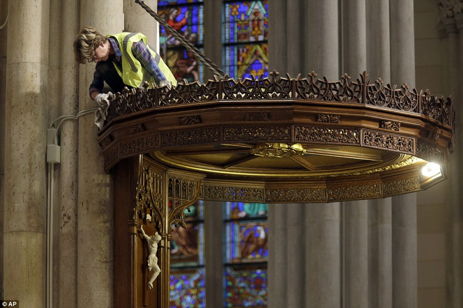 New Yorkers are bracing themselves for days of travel mayhem next week as one of the largest programs of road closures ever is due to be put into place when Pope Francis visits (pictured, a worker cleans and polishes the pulpit of St. Patrick's Cathedral)