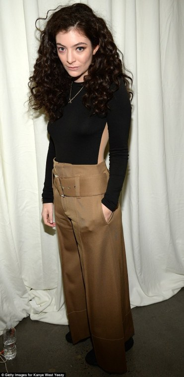 Putting her best foot forward! Wearing belted and flared camel pants, Lorde teamed her trousers with a black and beige long sleeve top that gave the appearance of having cut outs